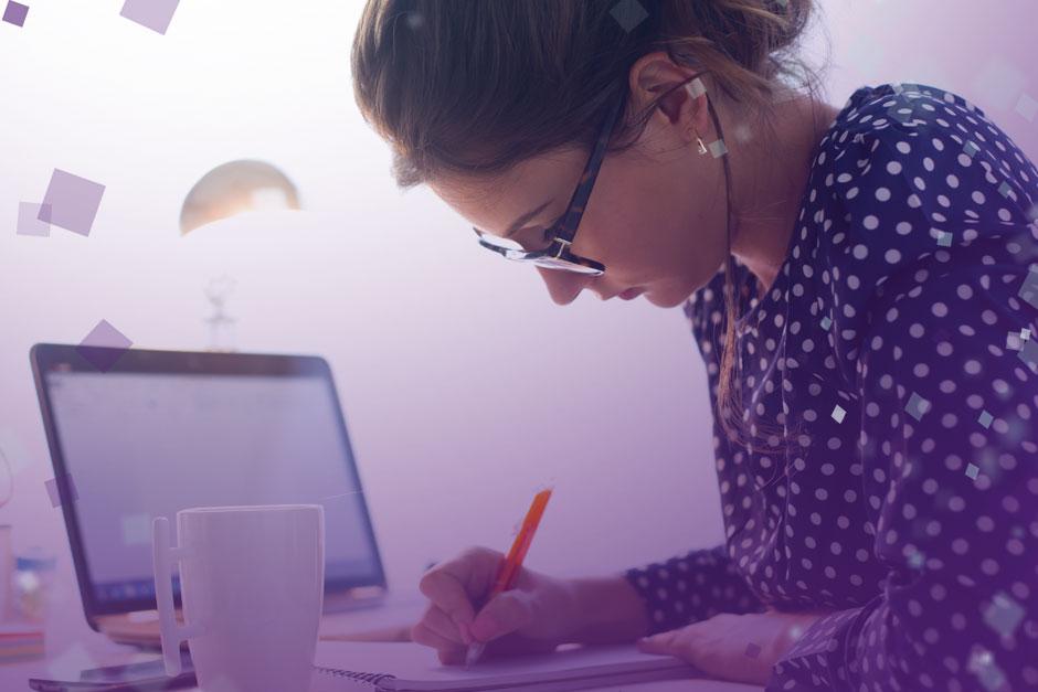 Woman writing next to laptop