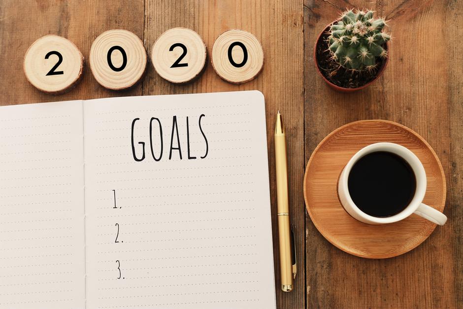 2020 goals written in notebook on desk with coffee mug